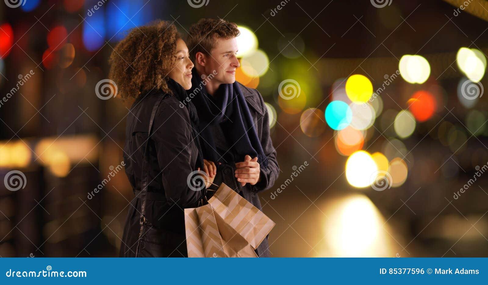 Atrakcyjny pary czekanie dla przejażdżki outdoors z torba na zakupy