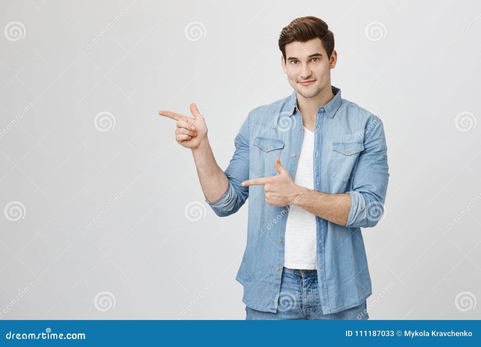 Atrakcyjny przystojny europejski facet wskazuje palce wskazujących z modnym ostrzyżeniem i szczerym uśmiechem, robi armatniemu ge