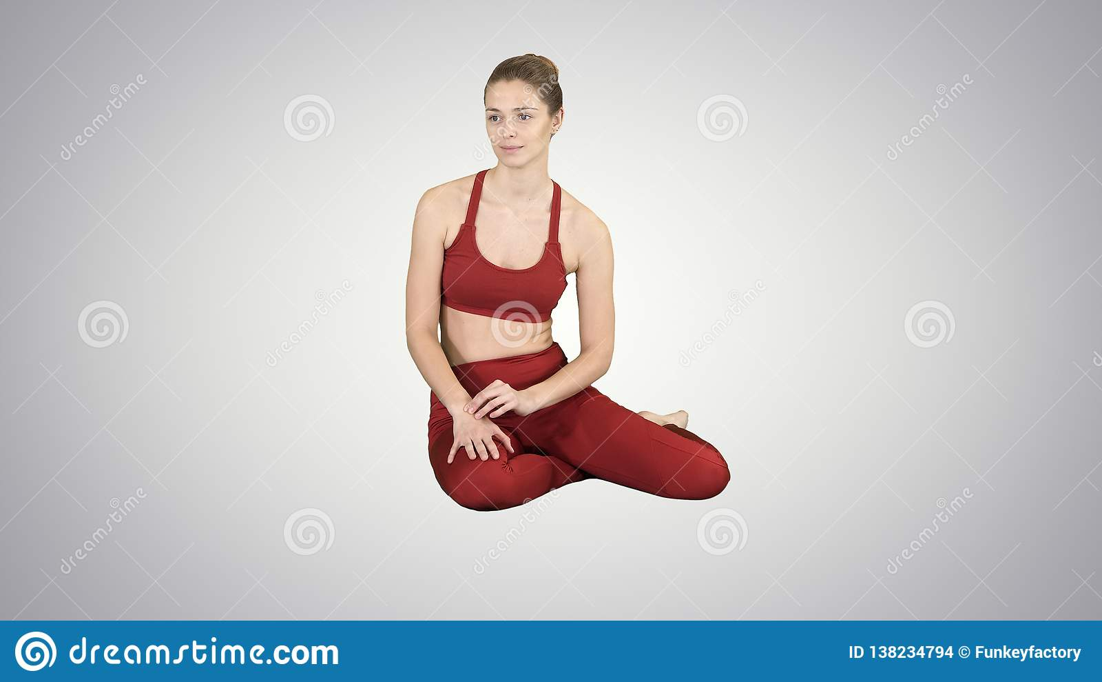 Atrakcyjny sprawności fizycznej kobiety obsiadanie na podłodze i słuchanie na gradientowym tle