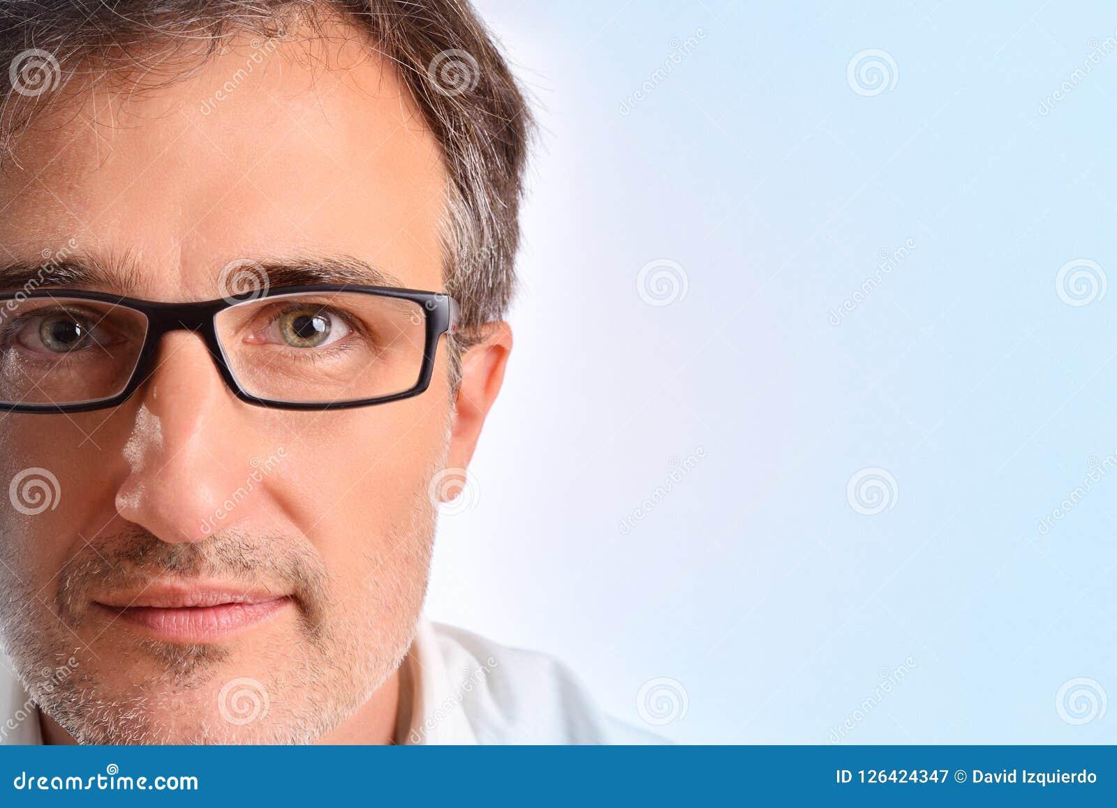 Atrakcyjny w średnim wieku mężczyzna z eyeglasses tła błękitnym detai