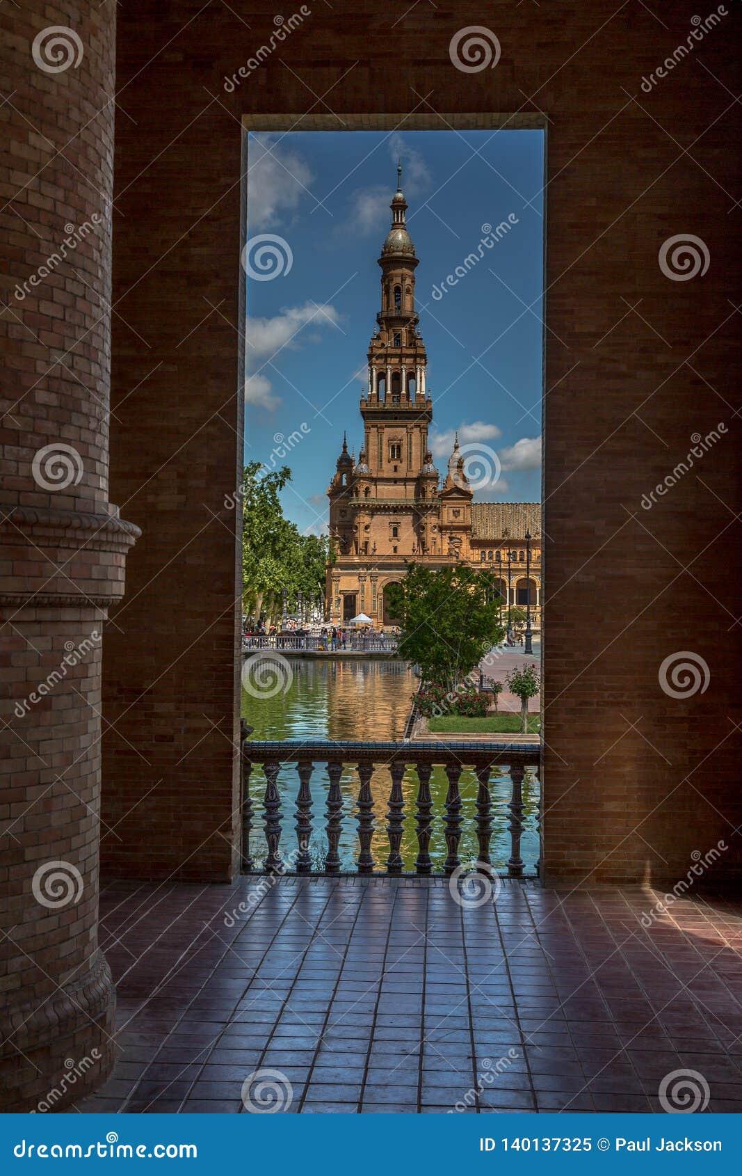 Através da arcada em Plaza de Espana em Sevilha, Espanha