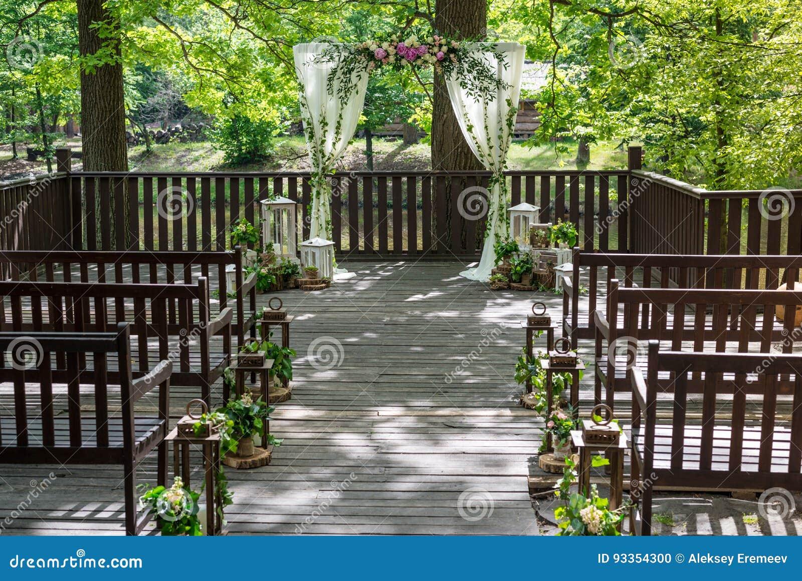 Atributos Wedding Cerimónia de casamento As colunas brancas de um casamento arqueiam, decorado com flores, e os bancos marrons Qu