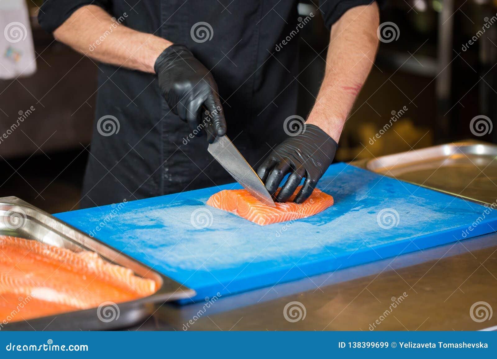 Att laga mat för tema är ett yrke av att laga mat Närbild av en Caucasian mans hand i ett restaurangkök som förbereder röda fiskf