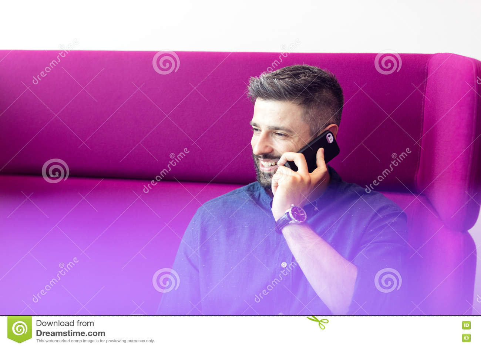 Att le den mitt- vuxna affärsmannen som talar på mobiltelefonen, medan sitta på lilor, uttrycker på kontoret