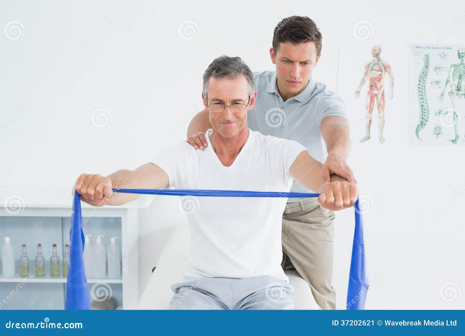 Att massera för terapeut mans skuldran i sjukhus