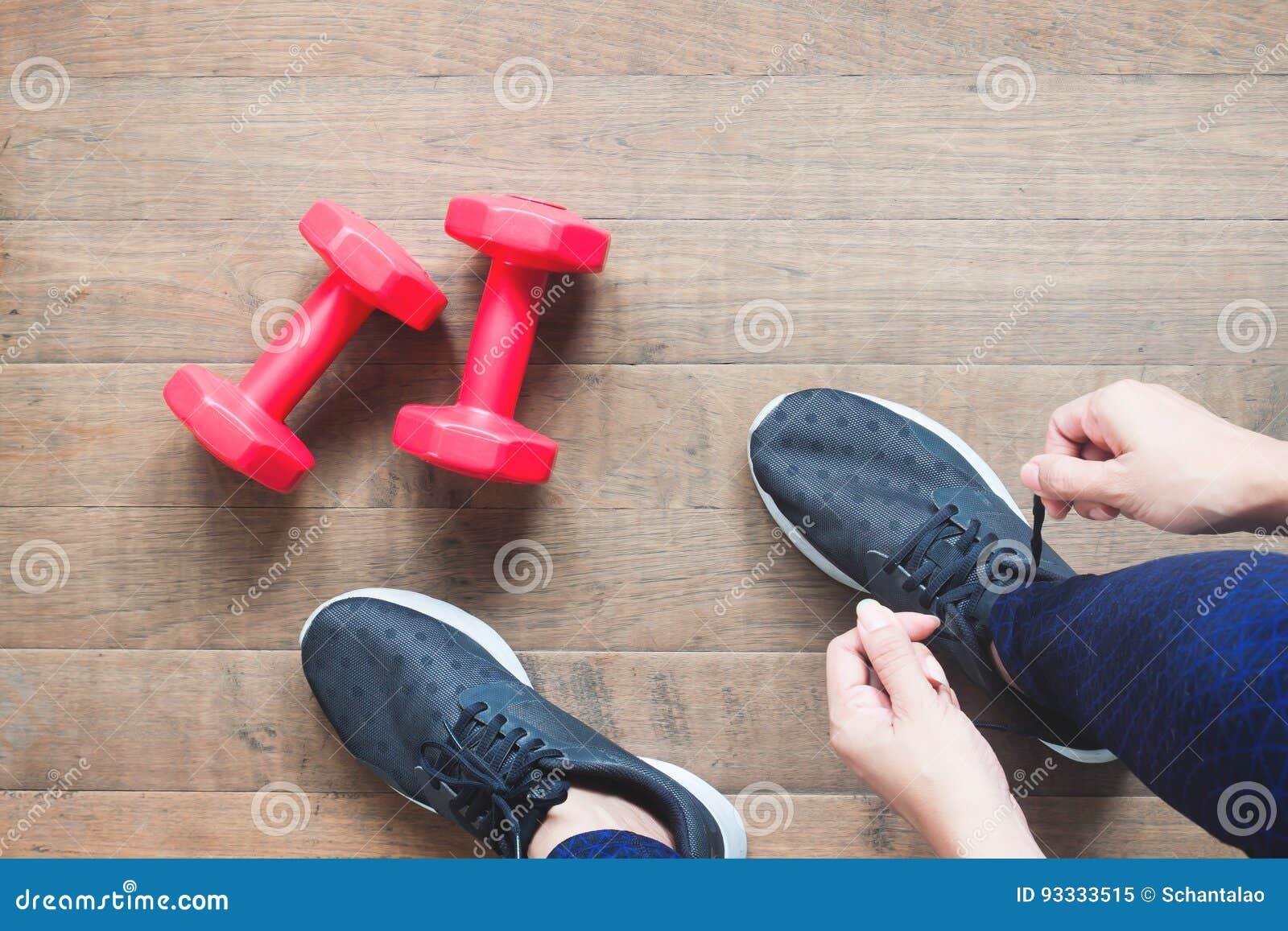Attachant des chaussures de sport, femme asiatique étant prête pour la formation de poids Exercice, formation de forme physique S