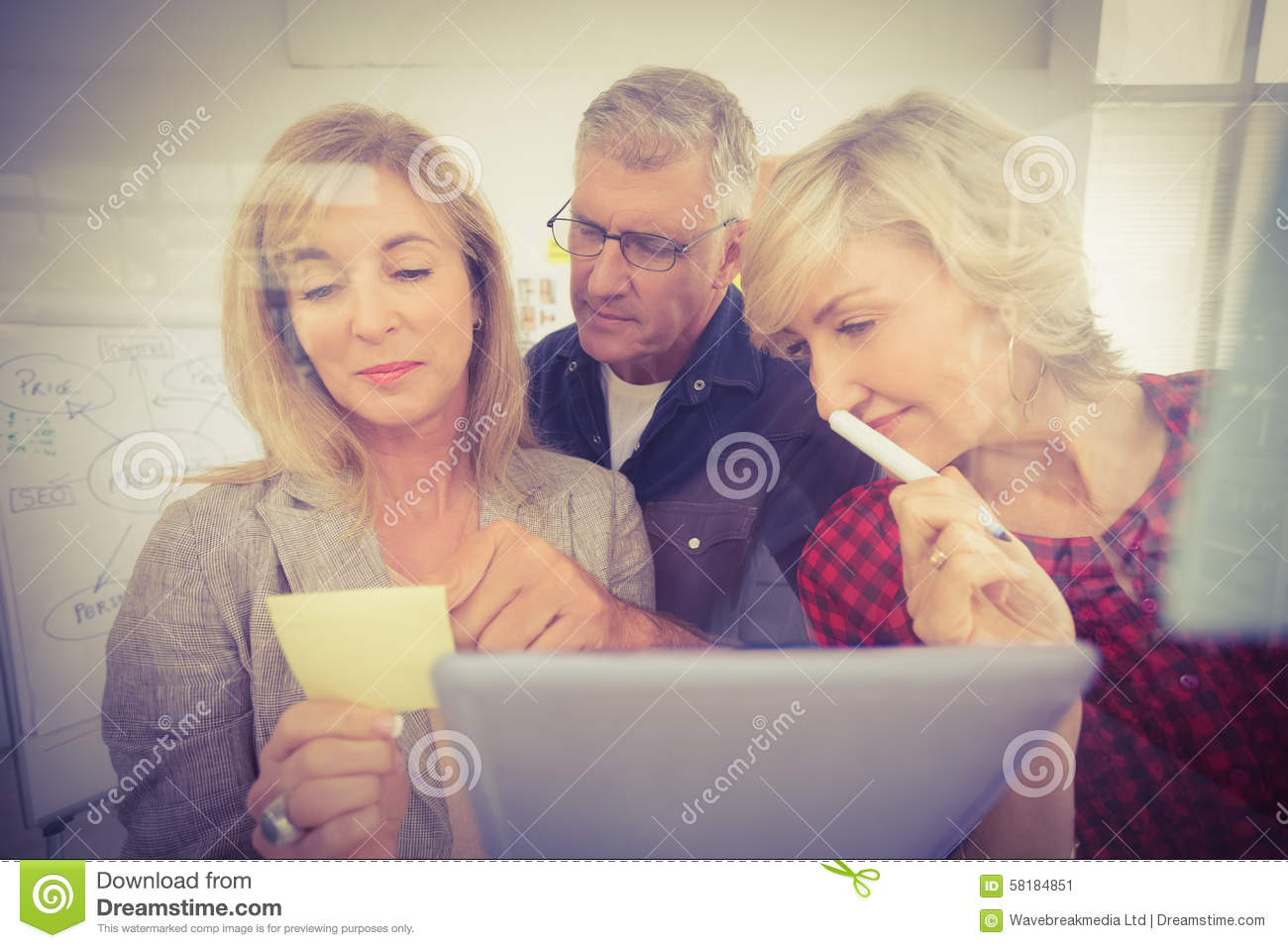 Attentive business team looking at a post it