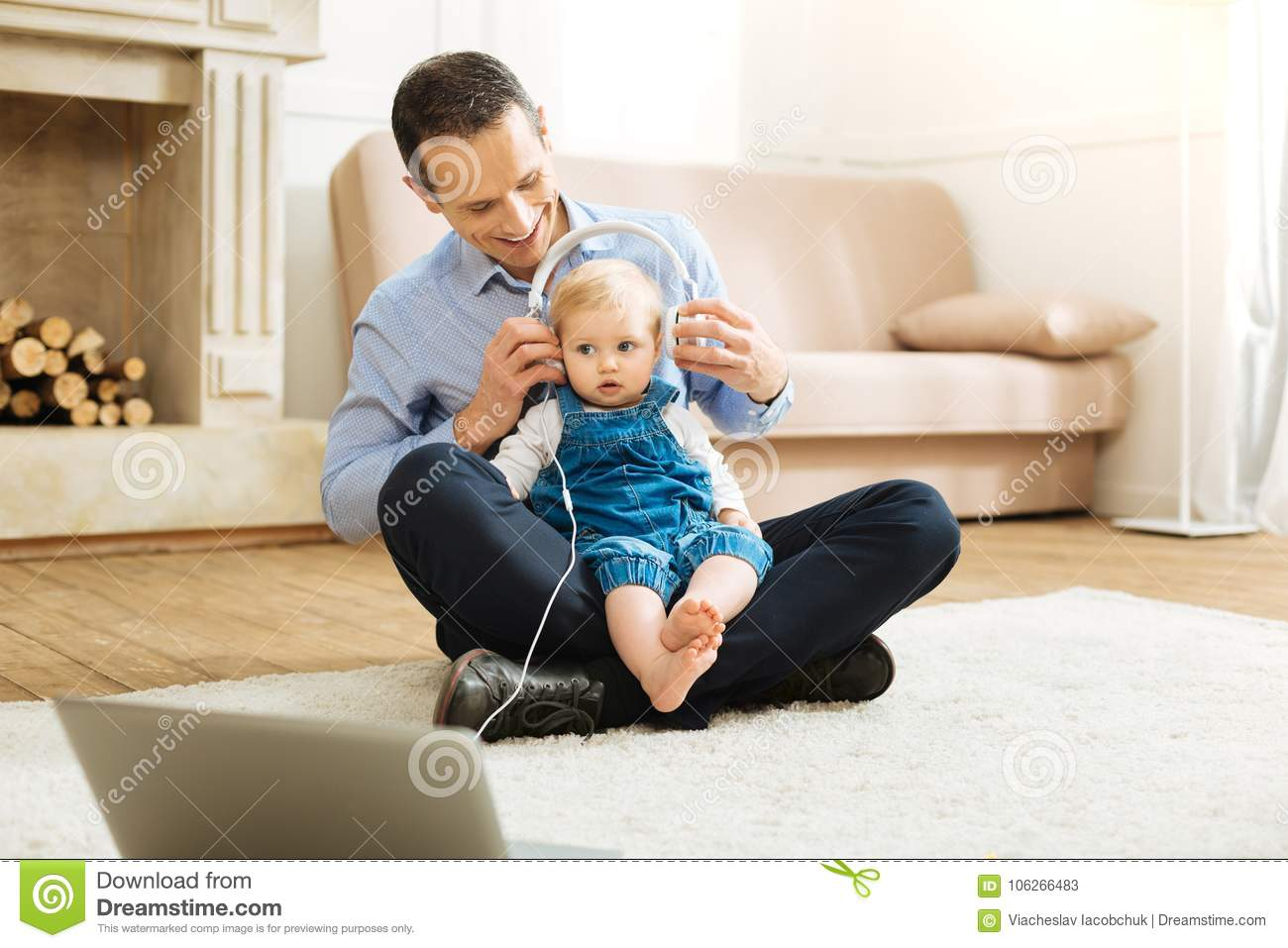 Attentive Cheerful Father Putting The Headphones On His Baby