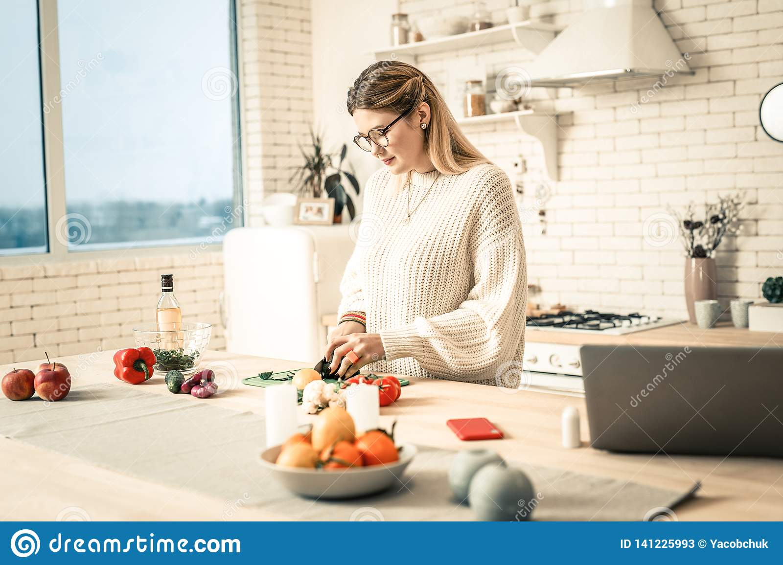 Attentive hard-working lady slicing vegetables during preparation process