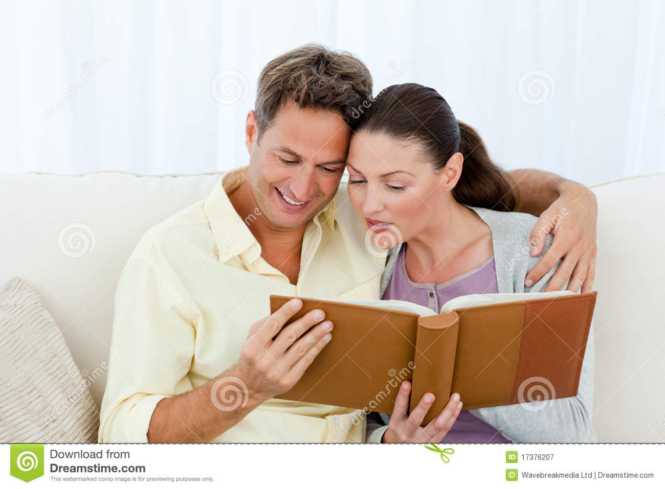 Attentive man and woman looking at a photo album