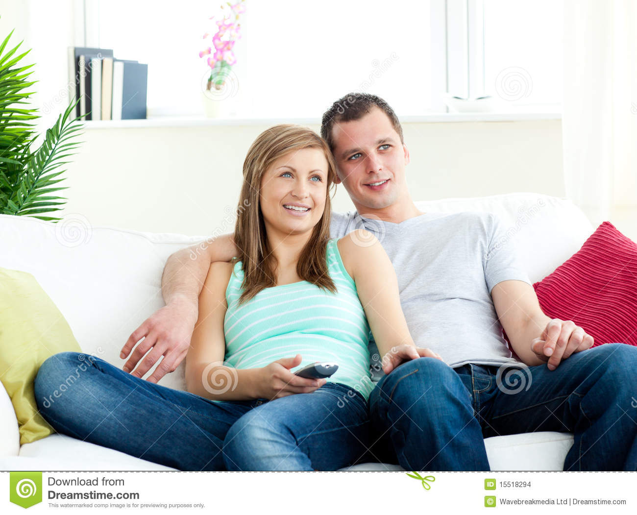 attentive young couple watching tv on the sofa stock photo image of remote love 15518294. Black Bedroom Furniture Sets. Home Design Ideas