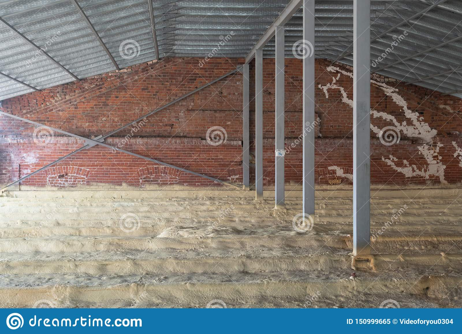 Attic of a house under construction with insulation on the floor. Pipes. Brick wall.