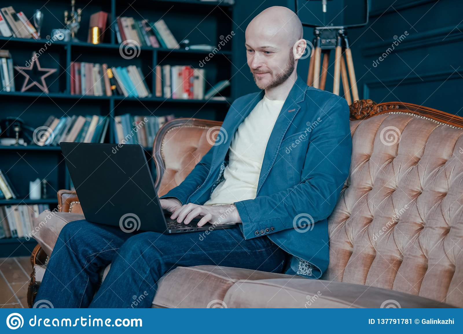 Attractive adult successful smiling bald man with beard in suit working at laptop on his rich cabinet