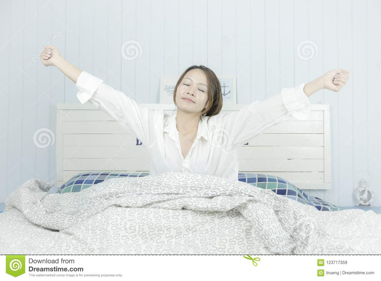 Beautiful asian woman listening to music. Listening Music Headphones Concept.Attractive asian woman awaking on the bed, sitting on