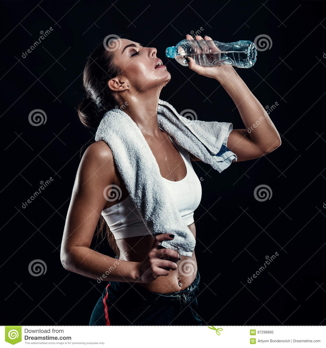 Attractive athletic young woman with perfect body drinking water from a bottle with towel around her neck against black background