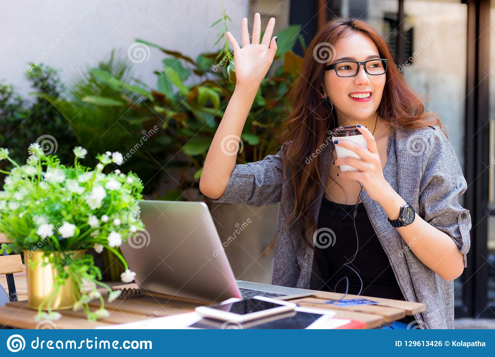 Attractive beautiful business woman is waving hand and saying he