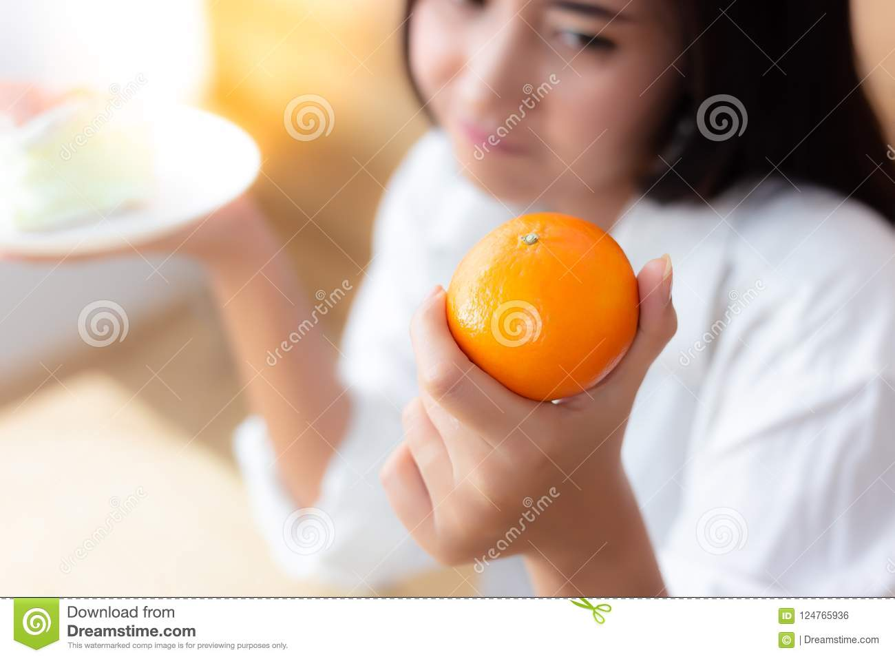 Attractive beautiful woman is holding orange and cake. Pretty fa