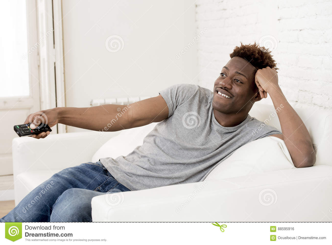 Attractive black african american man sitting at home sofa couch watching television
