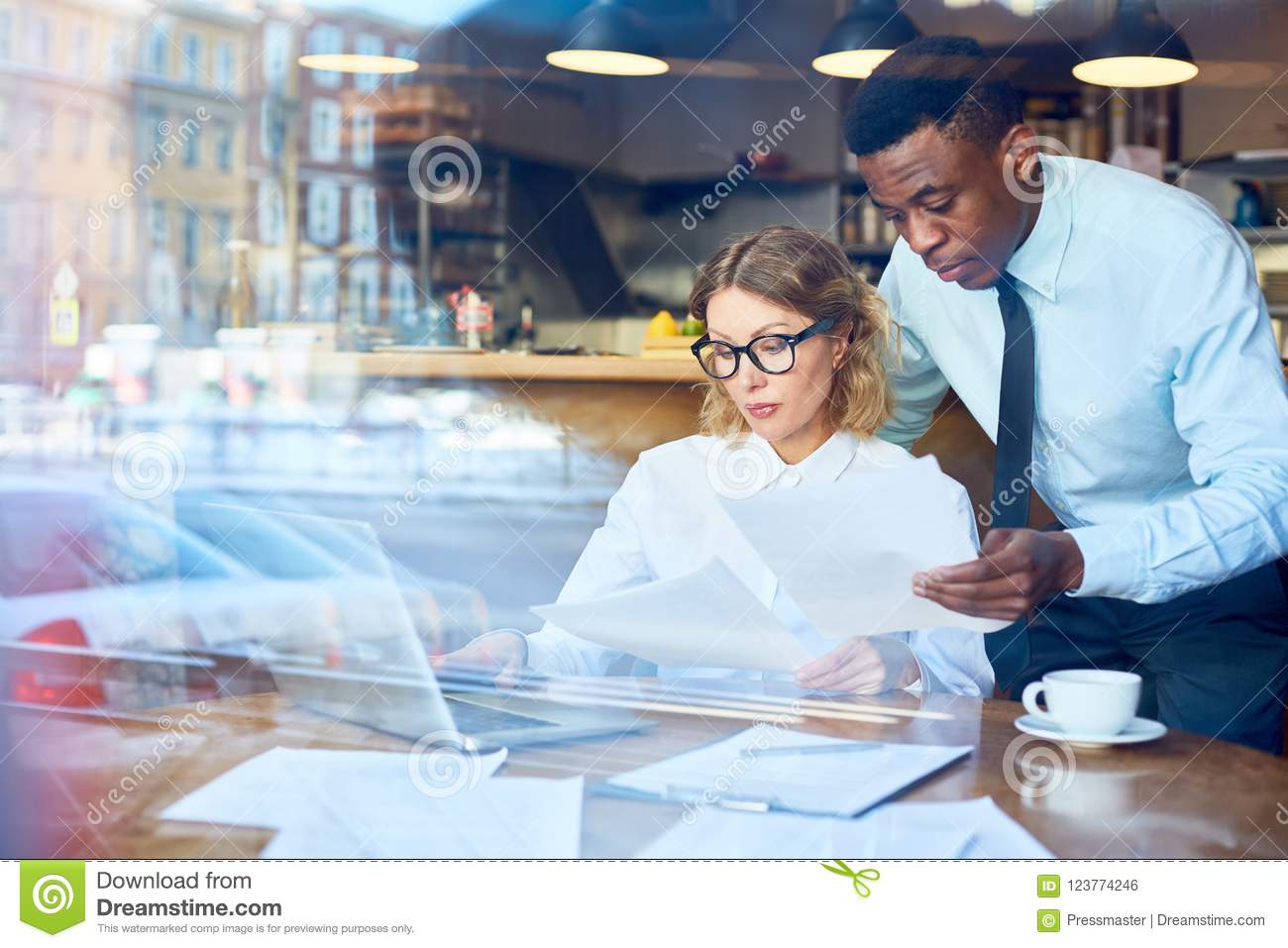 African-American Man Showing Paper To Colleague In Cafe