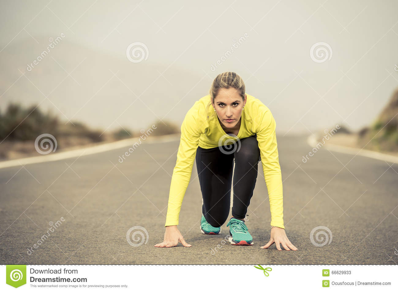 Attractive blond sport woman ready to start running practice training race starting on asphalt road mountain landscape