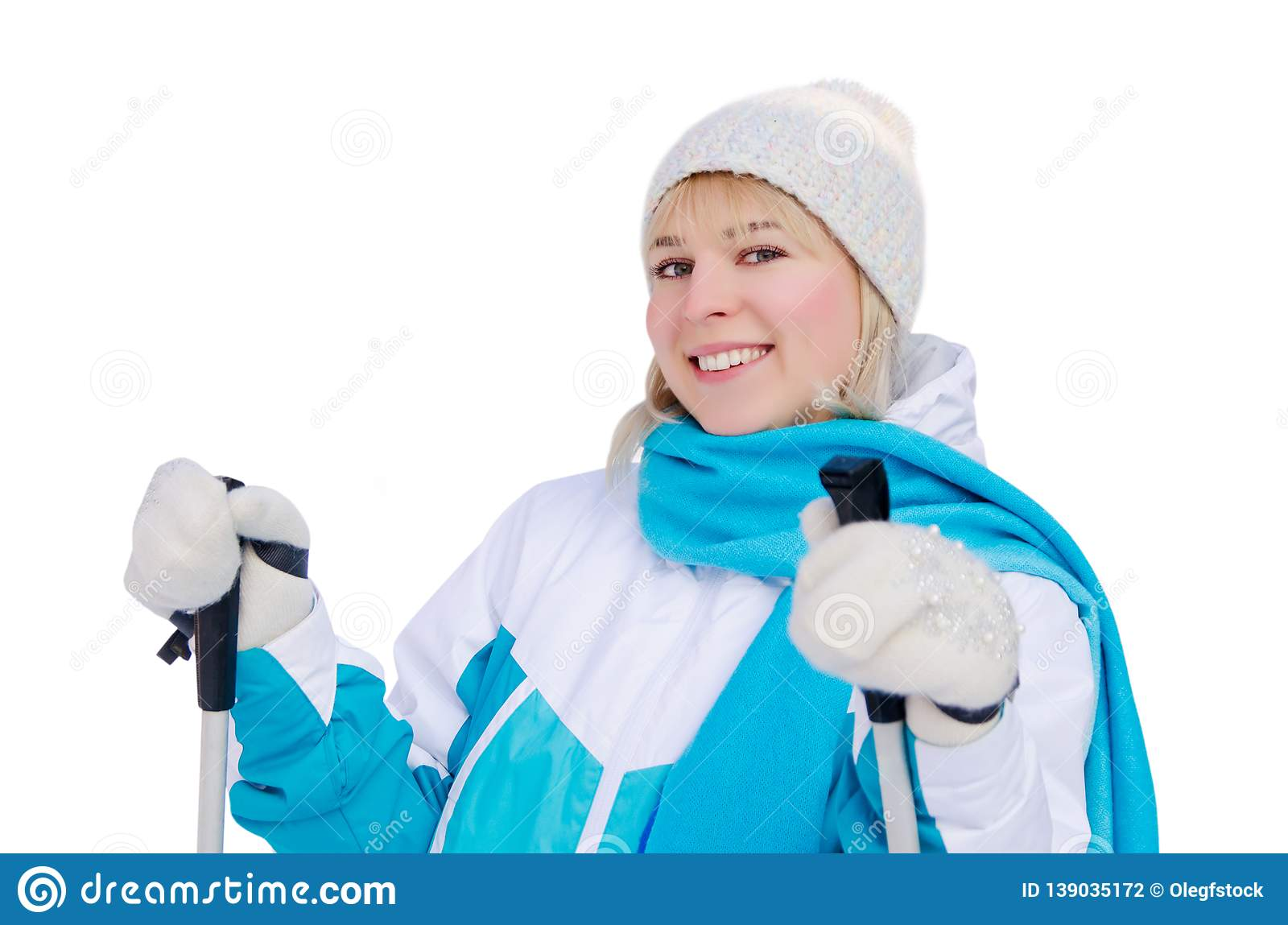 Attractive blonde girl in sports jacket, hat and blue scarf and ith ski poles in her hands with smile looking at the camera.