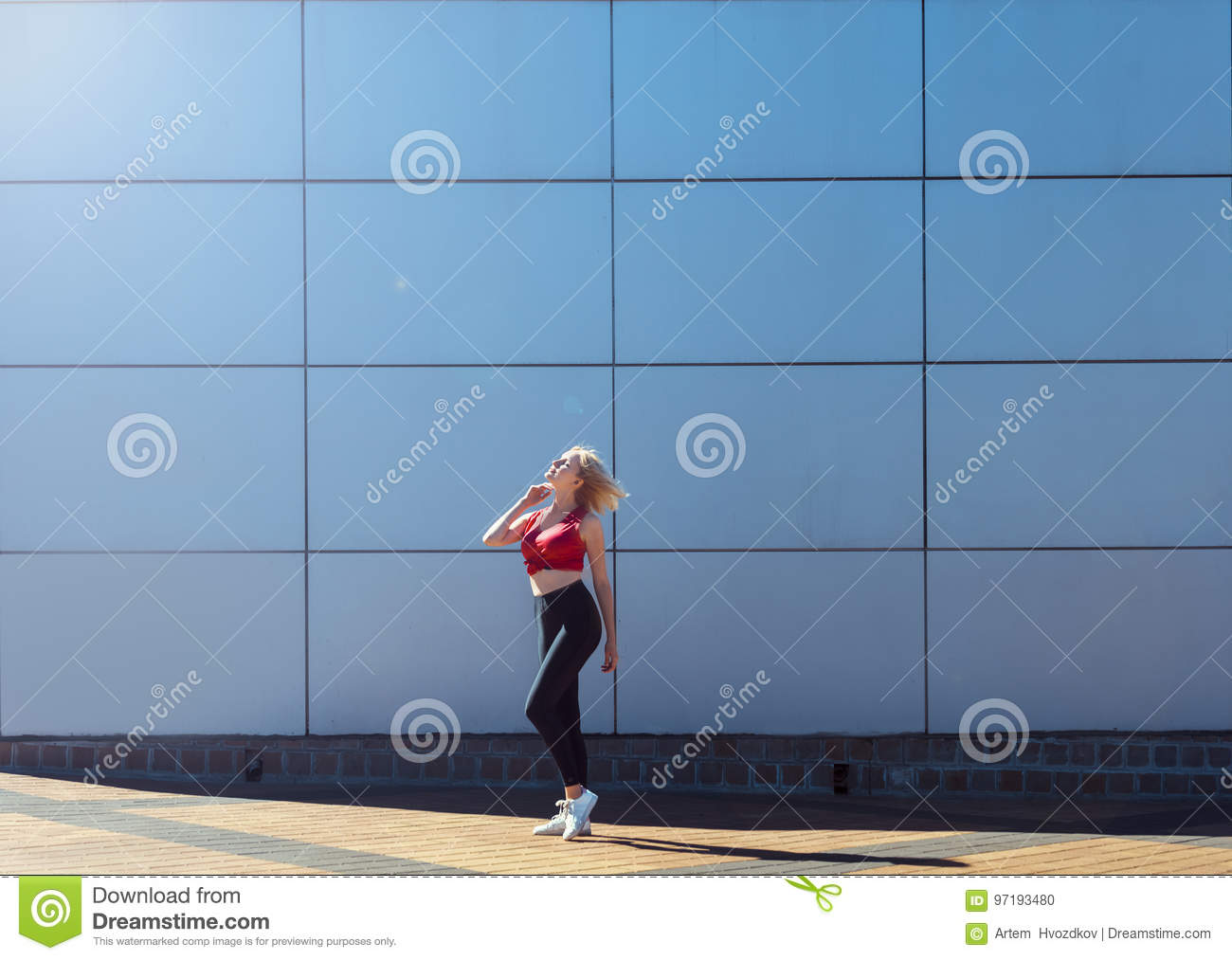 Attractive blonde in red top and black leggings posing in a stylish pattern. Day outdoor. Concept of sport life