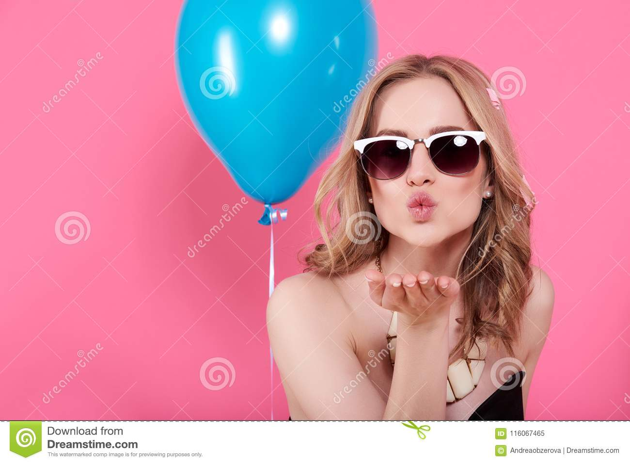 Attractive blonde young woman in elegant party dress and golden jewelry celebrating birthday and blowing a kiss towards camera.