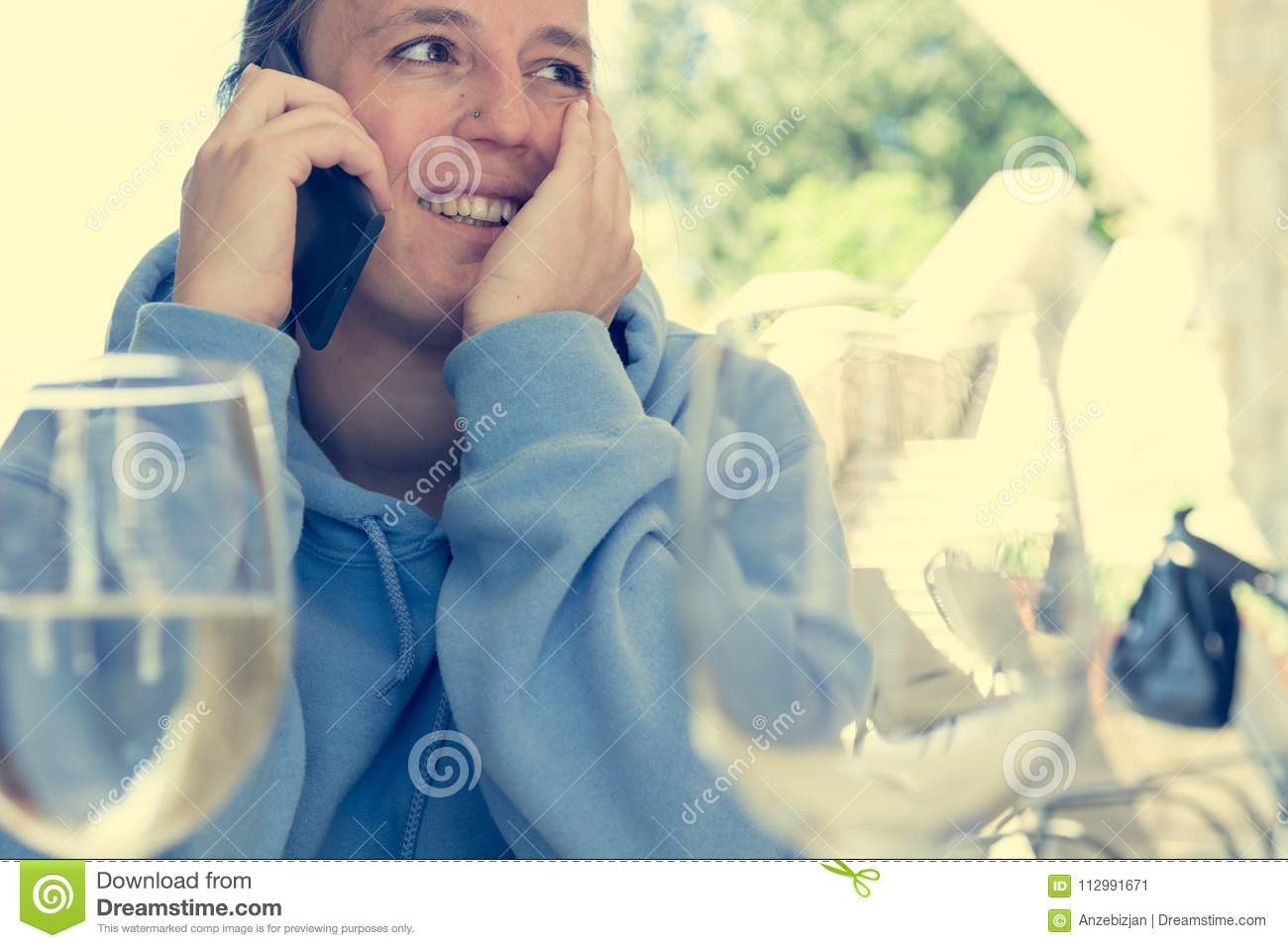 Attractive brunette taking a phone call in outdoor restaurant.