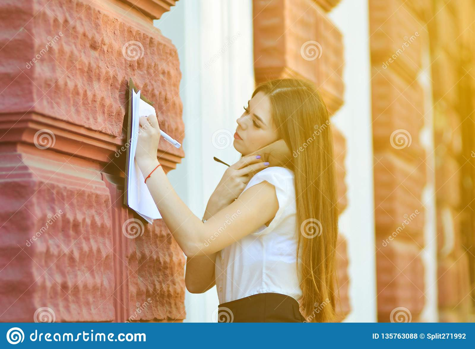 Attractive business lady talks on the phone and writes important information on paper. The working process.