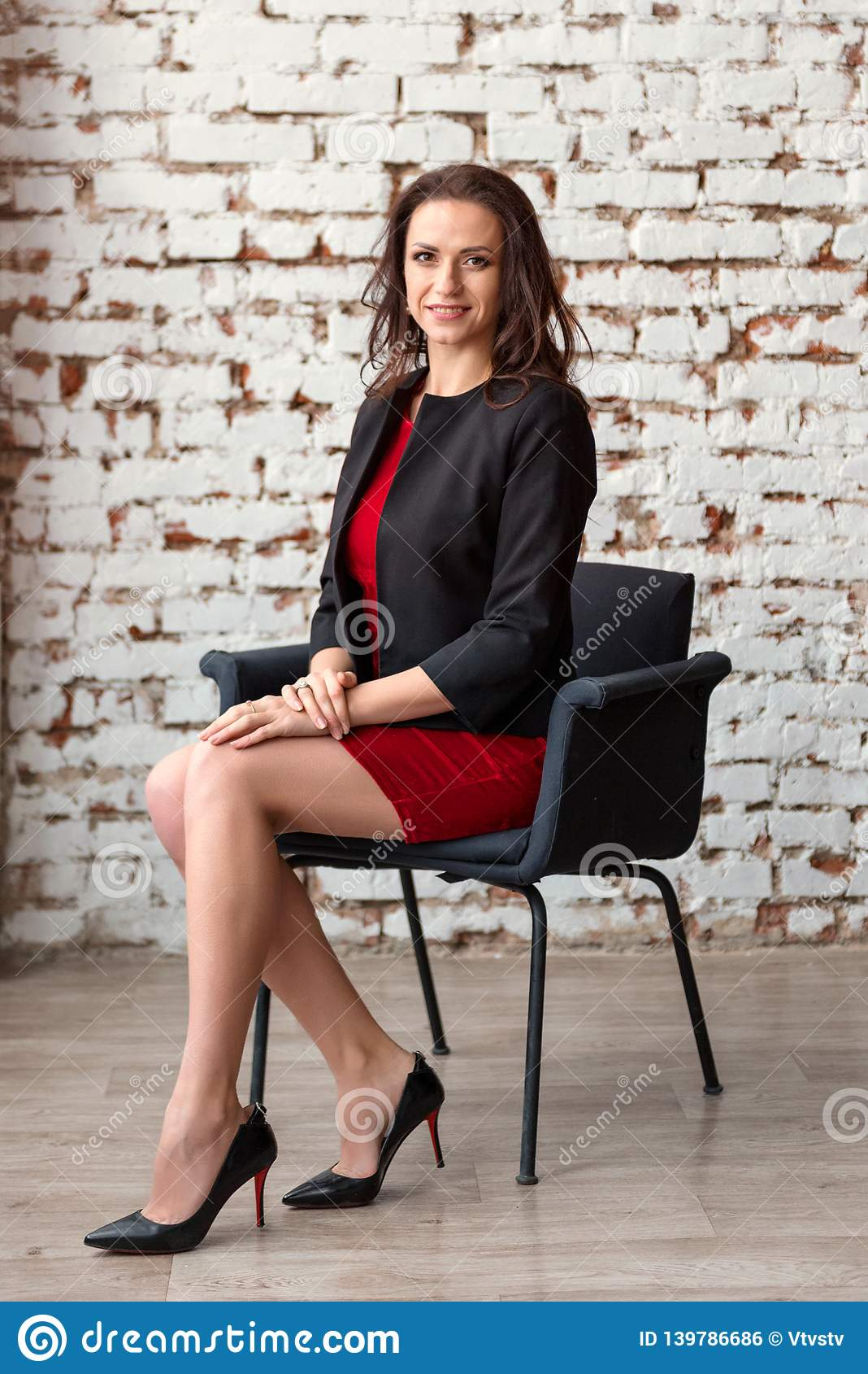 A young attractive business woman brunette in a short red dress and black jacket sitting on a chair with a white wall on the