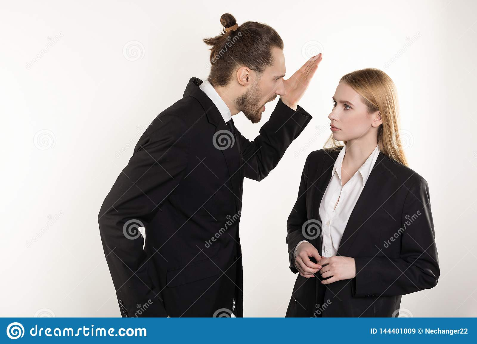 Attractive businessman with beard and trendy hairstyle in black suit screaming at his subordinate who can`t cope the