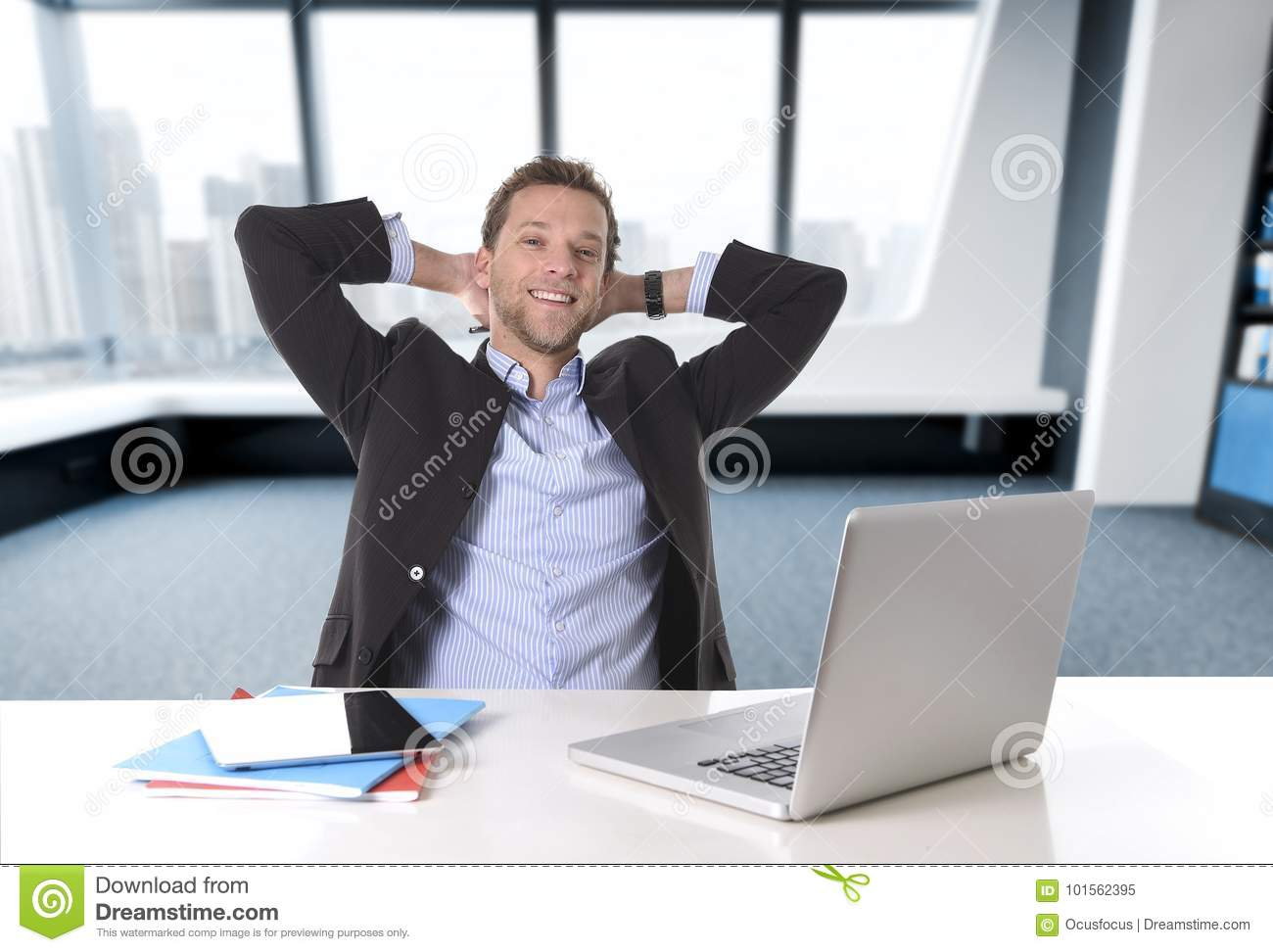 Attractive businessman happy at office work sitting at computer desk satisfied and smiling relaxed