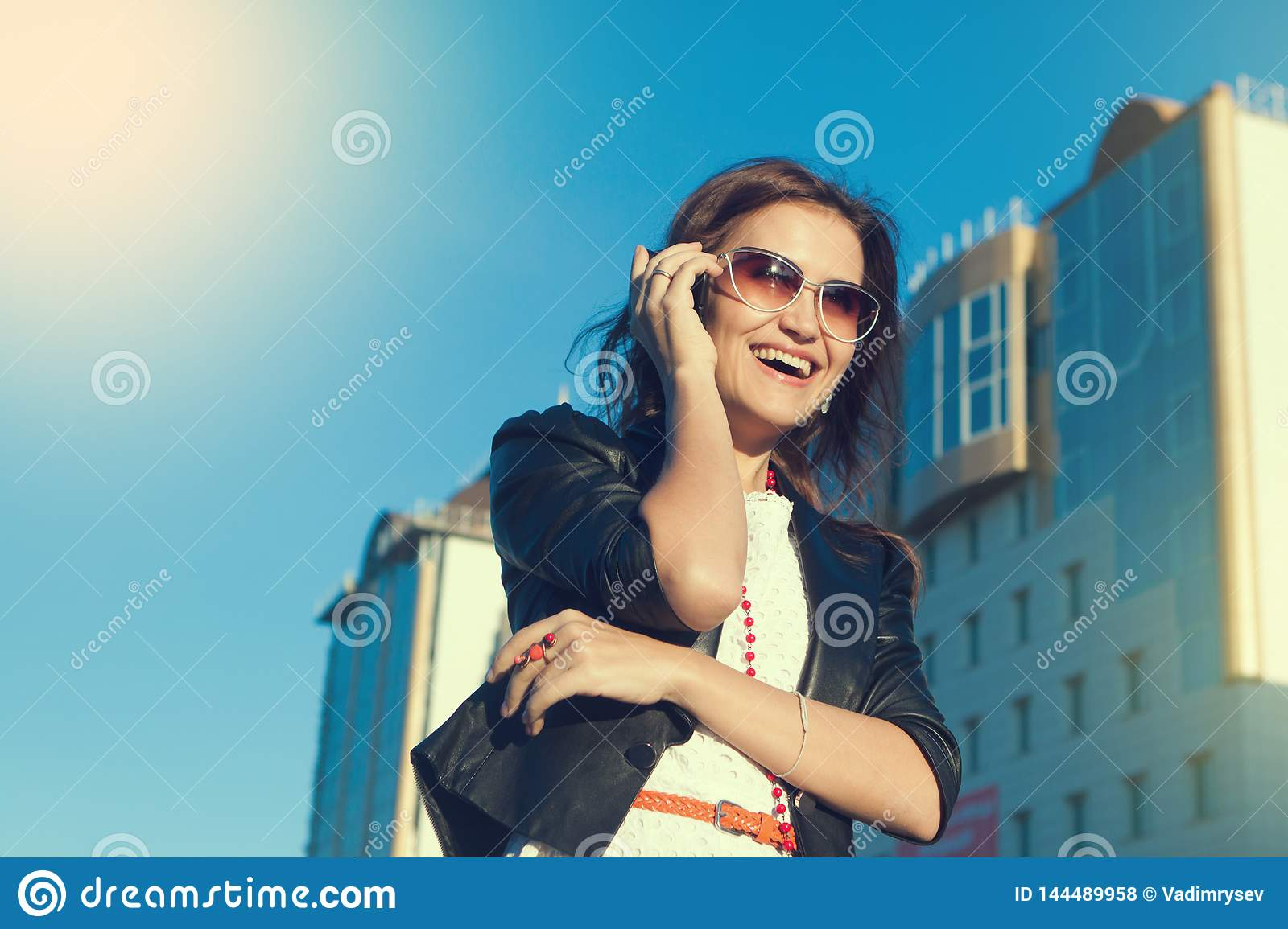 Attractive businesswoman using a cell phone in the city in sanny day.