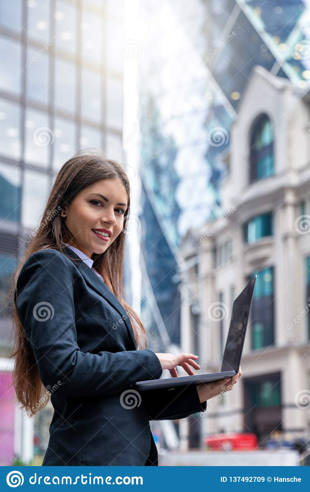 Businesswoman working on laptop outdoors in the City of London