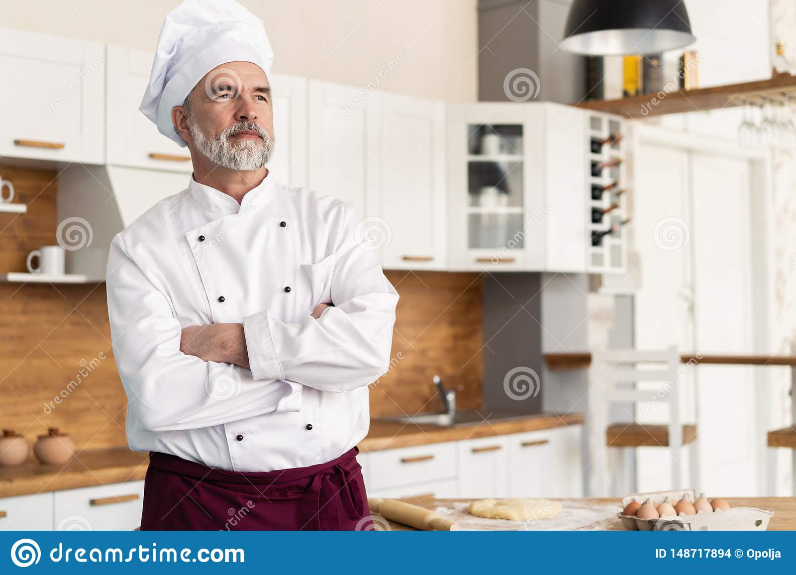 Attractive Caucasian chef standing with arms crossed in a restaurant kitchen