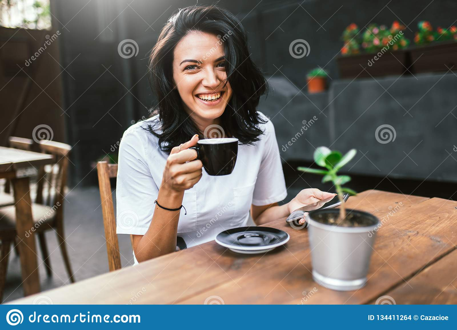Attractive Caucasian female with pleasant cheerful smile sitting at terrace cafe, drinking coffee and enjoying online
