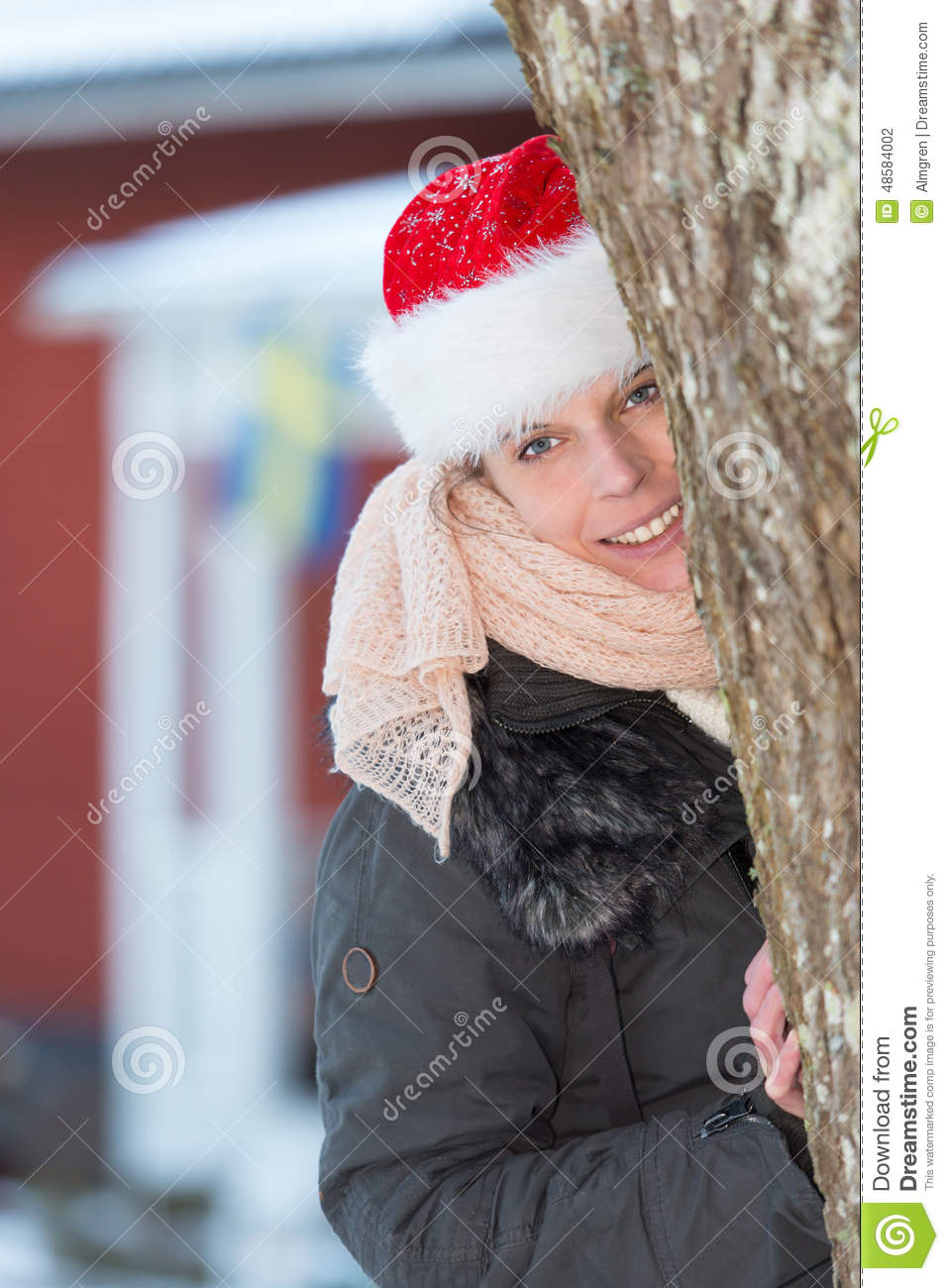 12268fbf9a Attractive happy woman with santa claus hat looking from behind a tree i  front of a typical red wooden house in Sweden.