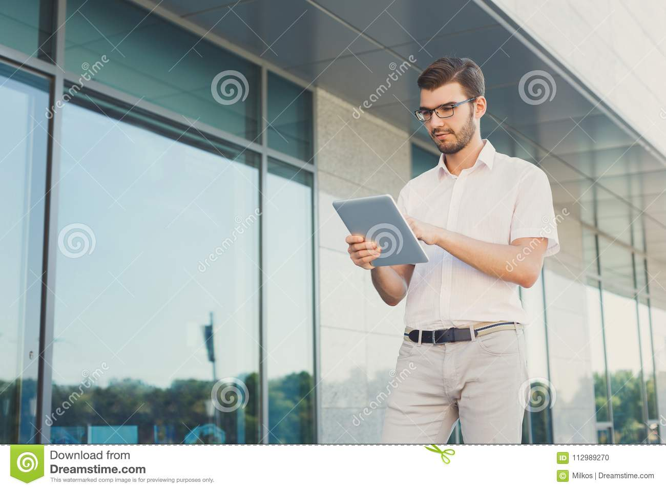 Pensive businessman using tablet outdoors