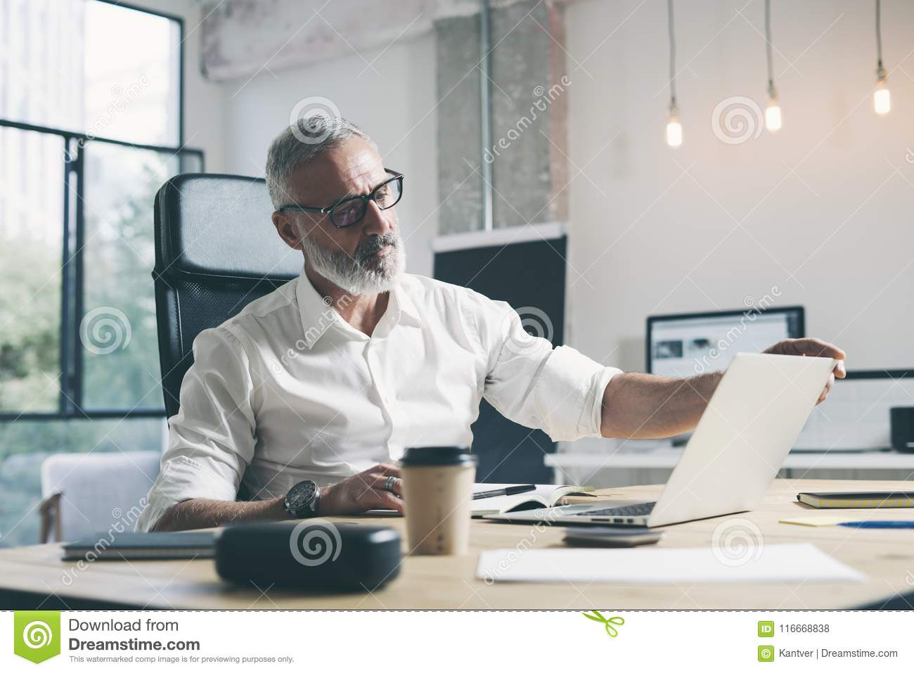 Attractive and confidental adult businessman using mobile laptop computer while working at the wooden table at modern