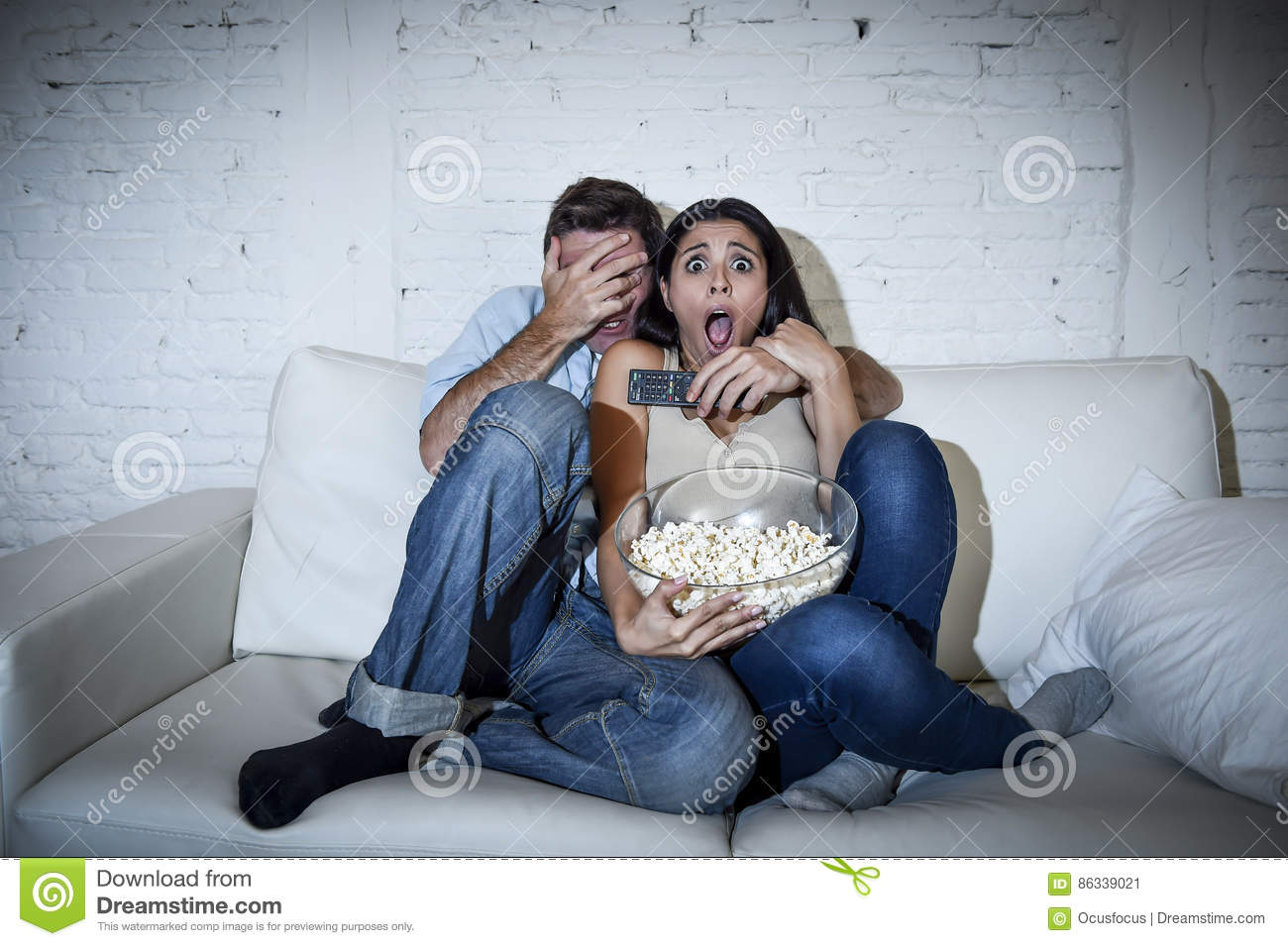 Attractive couple having fun at home enjoying watching television horror movie show