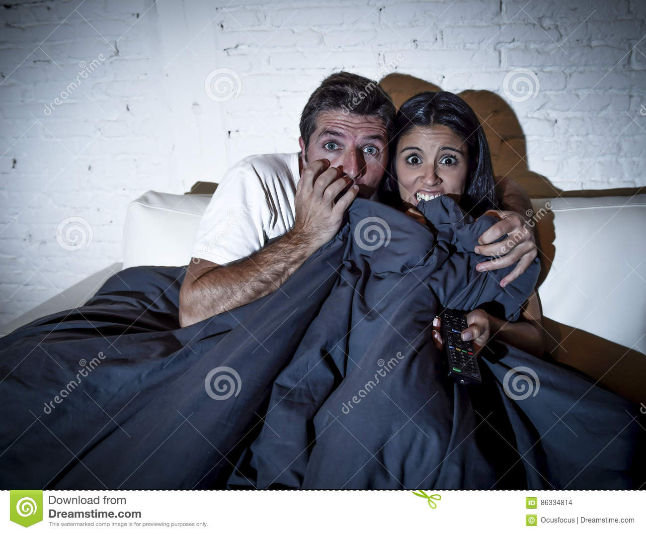 Attractive couple at home enjoying watching television horror movie covering with blanket