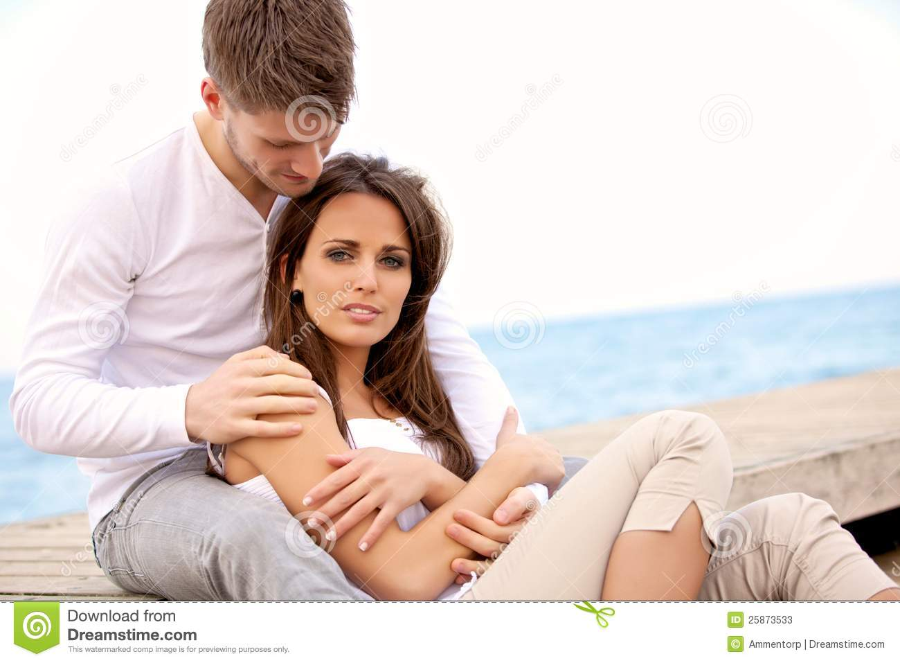Attractive Couple Sitting Together On A Pier Stock Photos