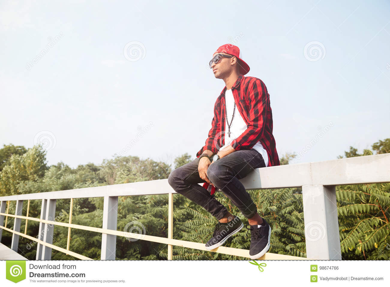 Download Attractive Dark Skinned Young Boy Sitting Against Nature Backgro Stock Photo - Image of people, glasses: 98674766