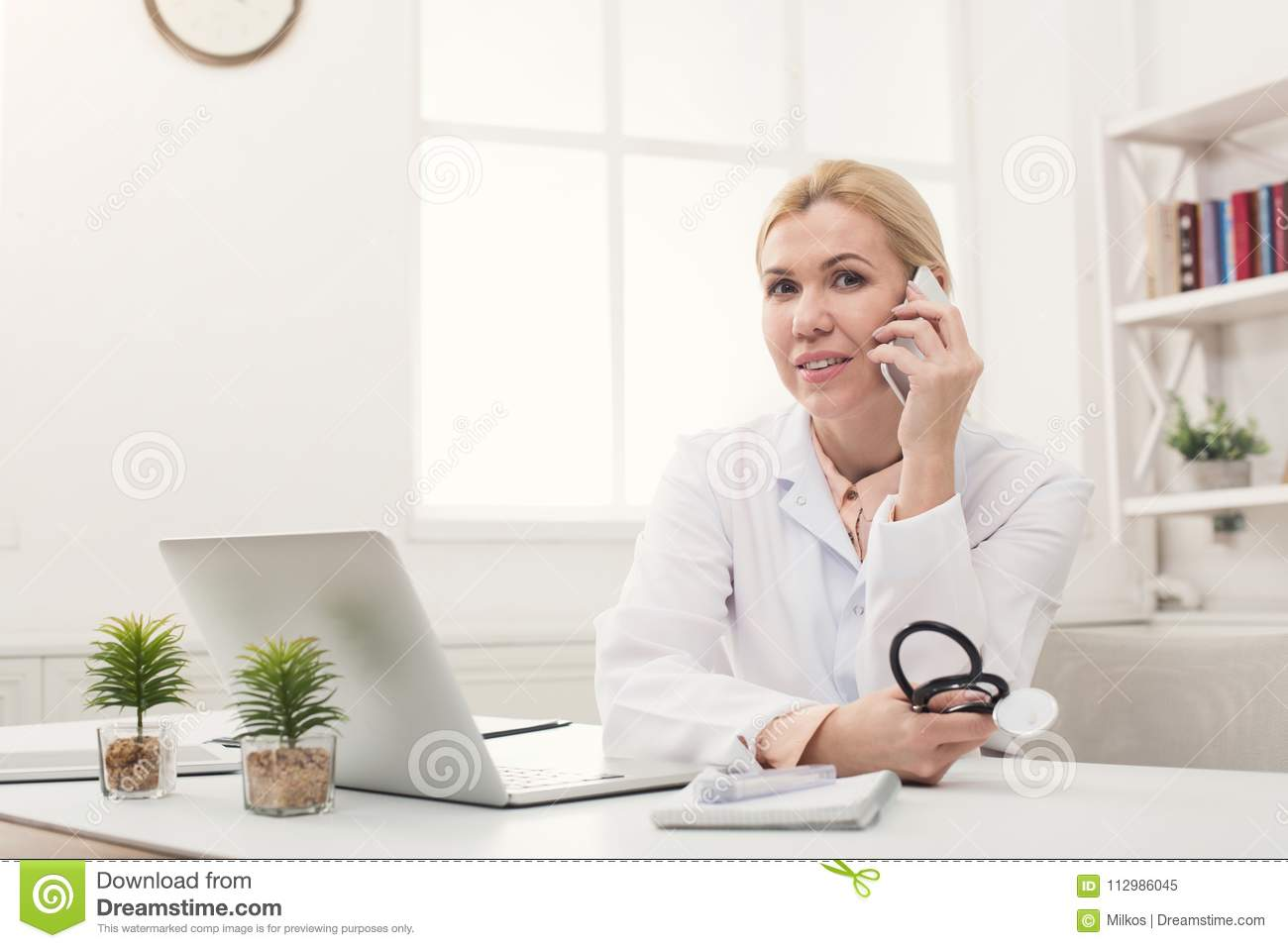 Attractive doctor talking on phone with patient
