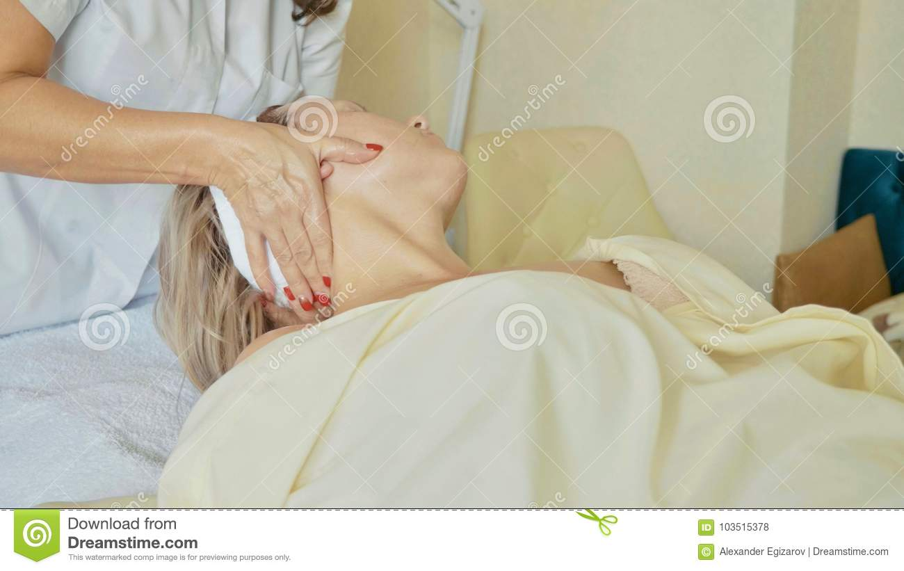 Attractive female at spa health club getting a facial procedure and massage