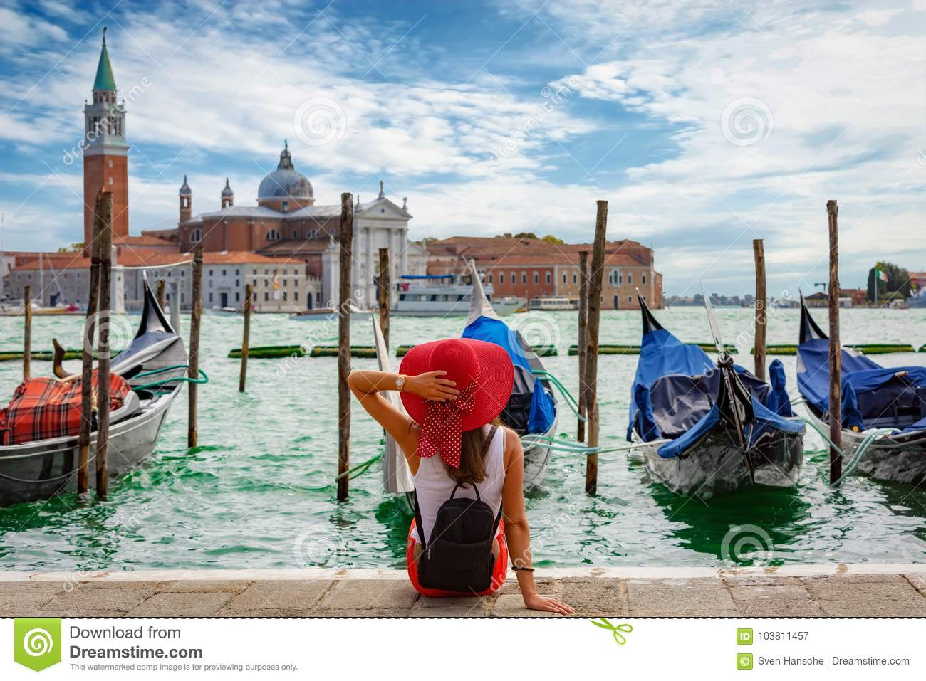 Attractive, female tourist enjoys the view from St. Mark`s Square in Venice, Italy