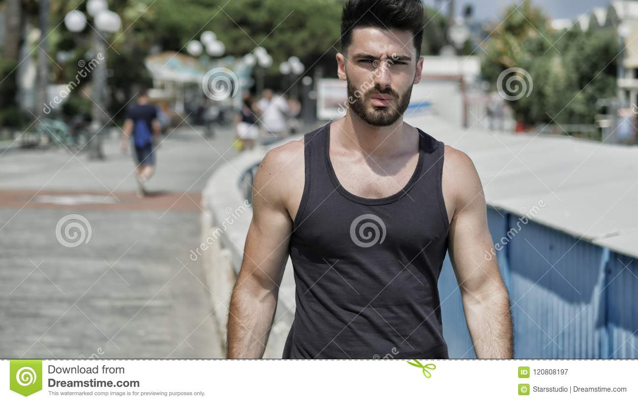 4b54e6e7951ff Attractive fit athletic young man soaking in the sun on seaside boardwalk  or seafront