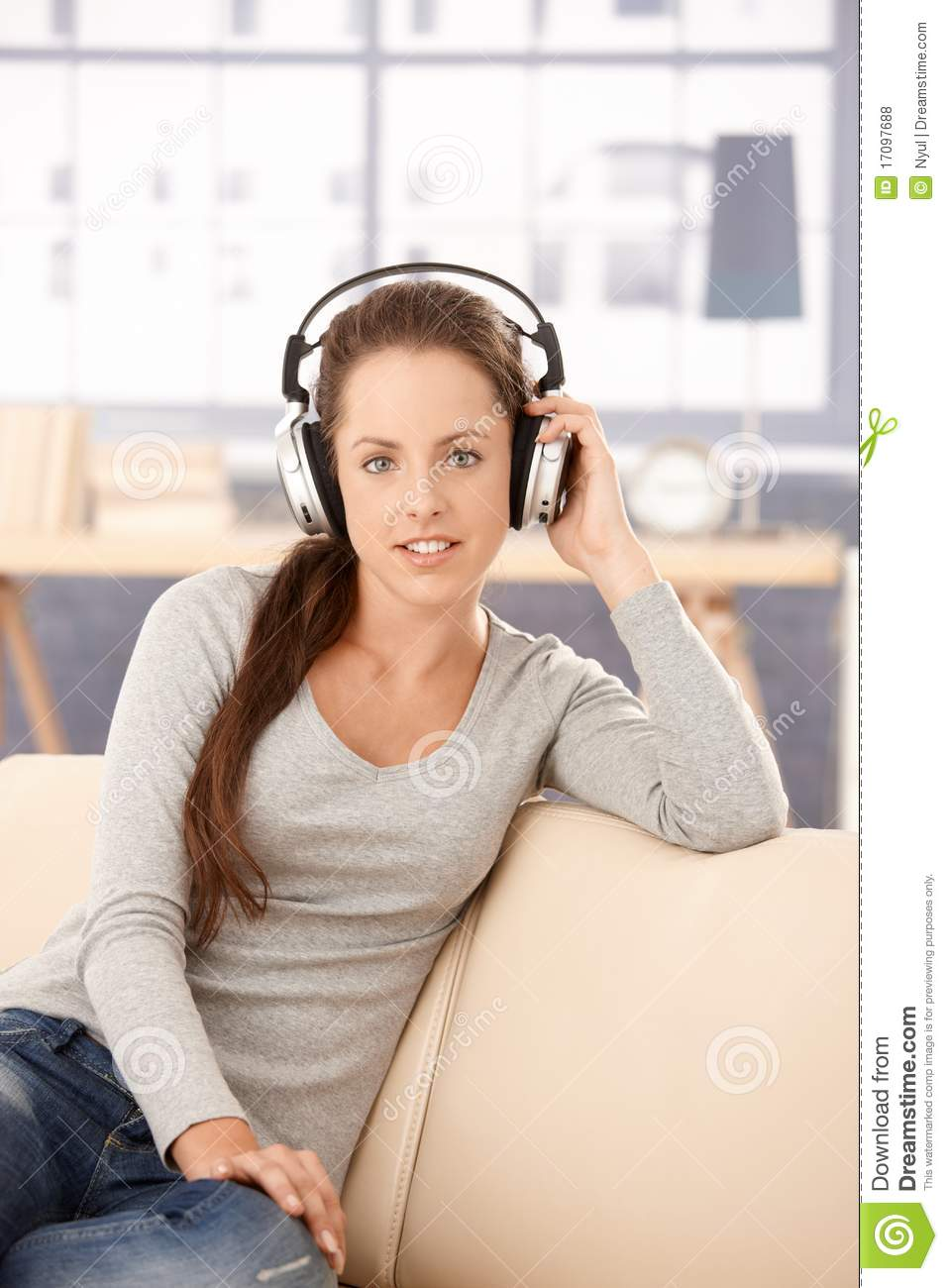 Attractive girl listening to music at home smiling