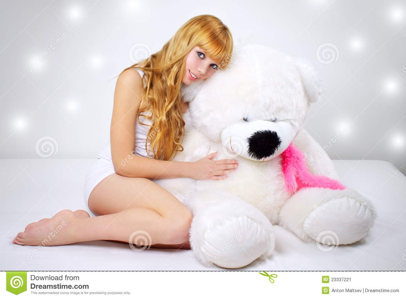 Attractive girl with a teddy bear on gray
