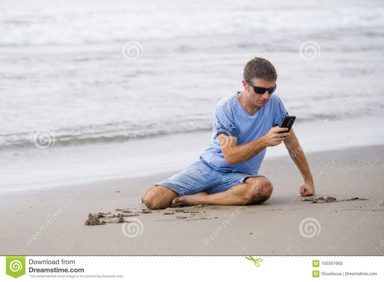 Attractive and handsome man on his 30s sitting on the sand relaxed on the beach laughing in front of the sea texting on mobile pho